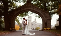 Bride and Groom under the stone arch at Shattuck St Mary's in Faribault, Minnesota